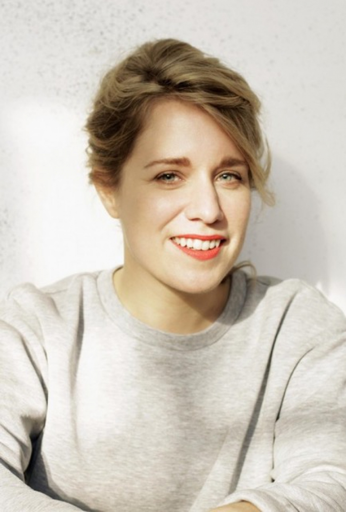 A portrait of a woman wearing a grey jumper with a white background